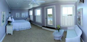 The Sunrise Suite -- Our largest guest suite is also the Grey Havens Inn's signature guest accommodation. Guests in the Sunrise Suite enjoy a king-size bed, a private bath and an incredible view of the ocean and coastline through three large windows and a French door leading to a private balcony.