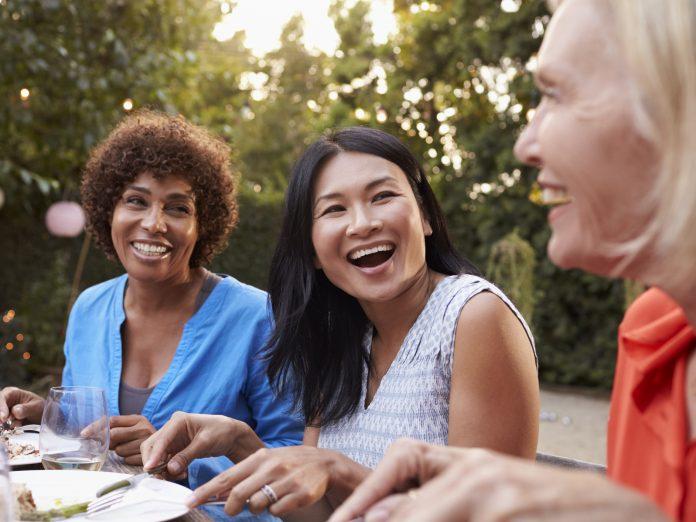 three women laughing and enjoying a New England girlfriends getaway.