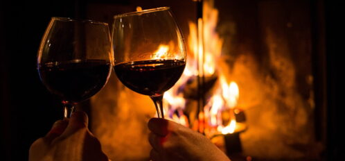 A couple holding a pair of wine glasses by the fireplace on Valentine's Day in Maine.