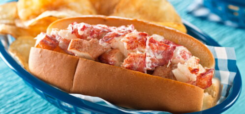 A delicious lobster roll with potato chips at one of the best lobster shacks in Maine.