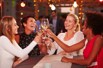 Four women toasting with wine