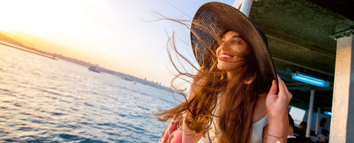 Woman smiling on boat at sunset
