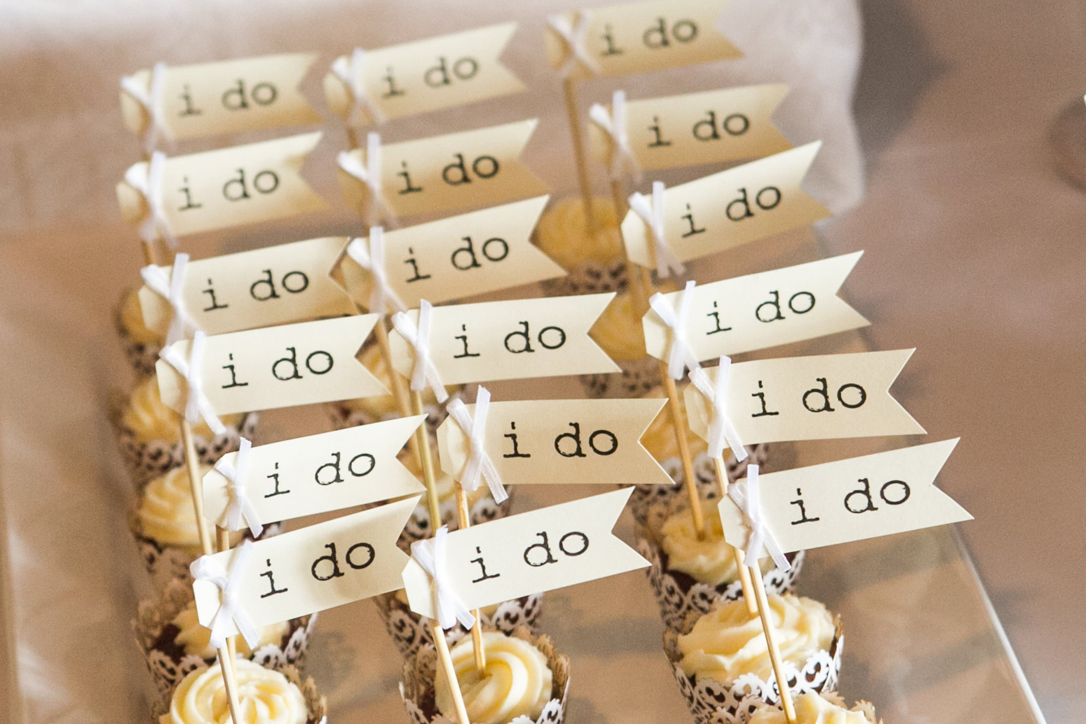 A row of Row of 'I Do' wedding cupcakes.
